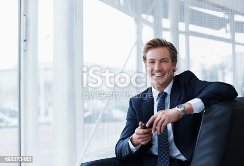 Portrait of happy businessman holding mobile phone while sitting in office