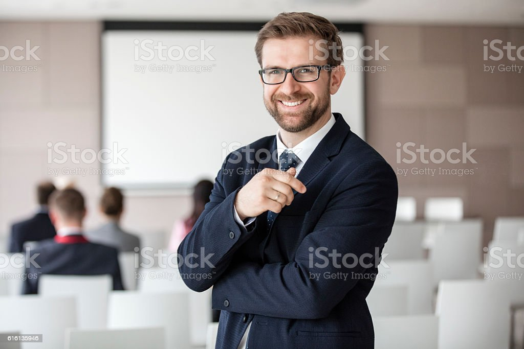 Portrait of happy businessman standing in seminar hall stock photo