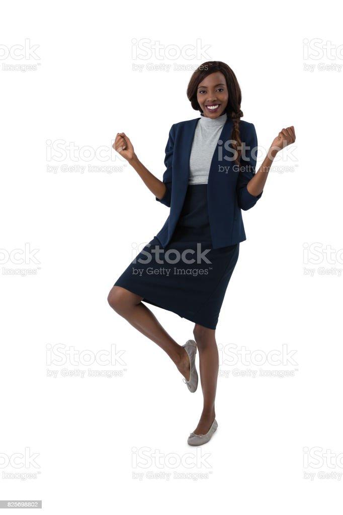 Portrait of happy businesswoman standing on one leg stock photo