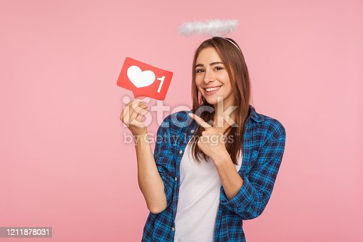 640248524 istock photo Portrait of happy charming girl with angelic halo smiling and pointing at social media like icon 1211878031
