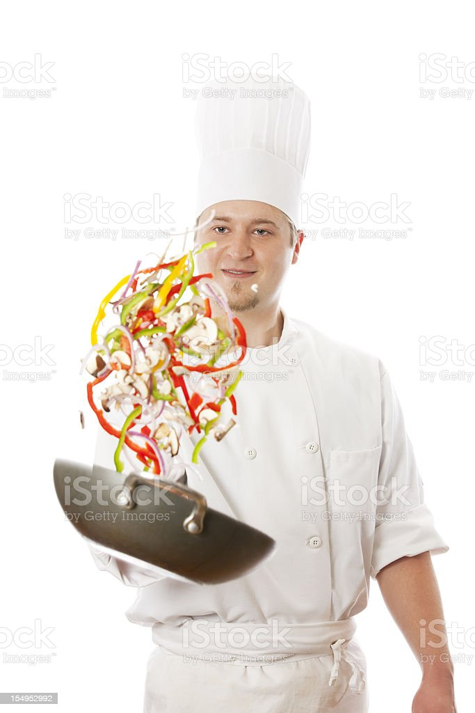 Portrait of happy chefs tossing vegetables in a wok stock photo