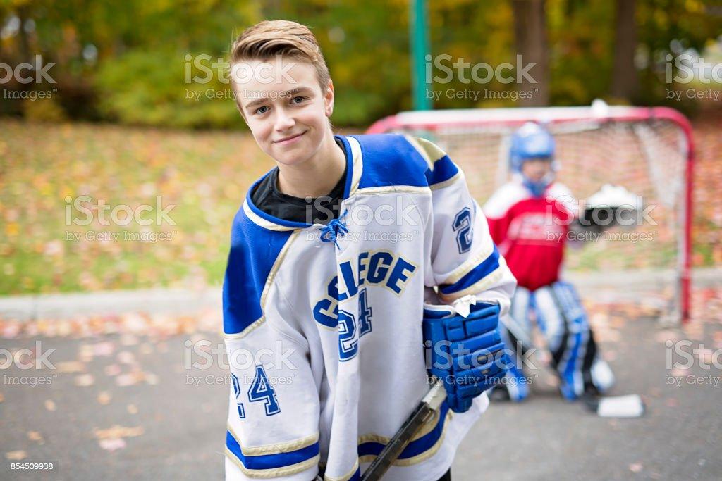 portrait of happy child play hockey outside stock photo