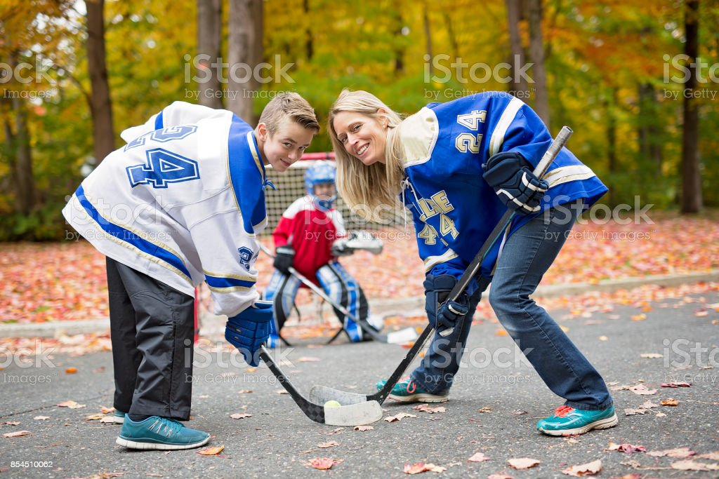 portrait of happy child play hockey outside with mother stock photo