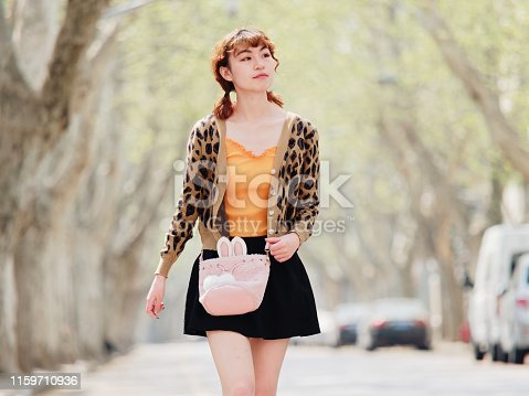 istock Portrait of happy Chinese girl in short skirt walking on sunny road, smiling and looking for something interesting. 1159710936