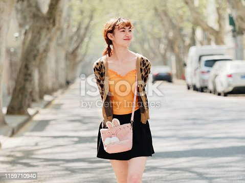 istock Portrait of happy Chinese girl in short skirt walking on sunny road, smiling and looking for something interesting. 1159710940