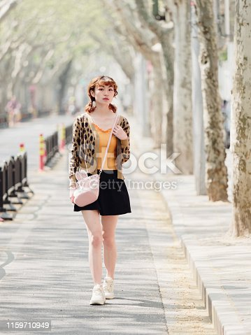 istock Portrait of happy Chinese girl in short skirt walking on sunny road, smiling and looking for something interesting. 1159710949
