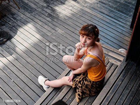 943759290 istock photo Portrait of happy Chinese girl in yellow halter top and short skirt sitting on stairs and smiling at camera, carefree young lady enjoy her leisure time in Wukang road in Shanghai, high angle view. 1188407324