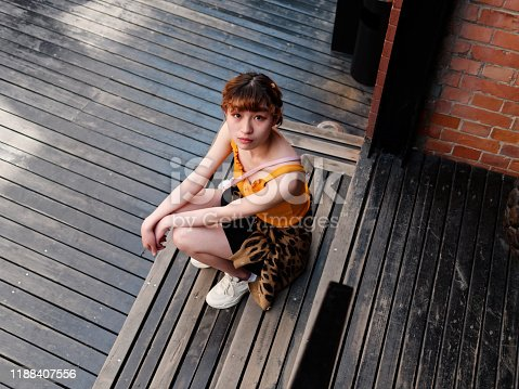 943759290 istock photo Portrait of happy Chinese girl in yellow halter top and short skirt sitting on stairs and smiling at camera, carefree young lady enjoy her leisure time in Wukang road in Shanghai, high angle view. 1188407556