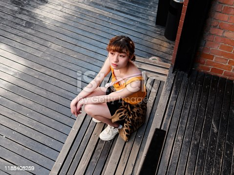943759290 istock photo Portrait of happy Chinese girl in yellow halter top and short skirt sitting on stairs and looking away, carefree young lady enjoy her leisure time in Wukang road in Shanghai, high angle view. 1188408259
