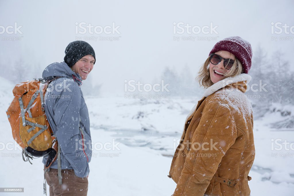 Portrait of happy couple in mountains during snowstorm stock photo