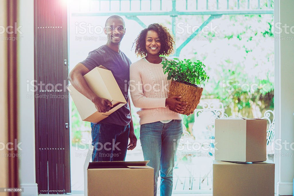 Portrait of happy couple moving house stock photo