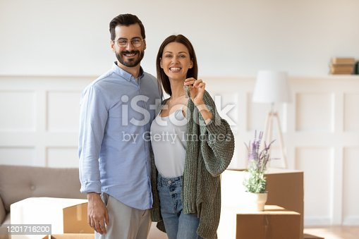 Portrait of excited young couple hug look at camera smile show house keys to new apartment moving in together, happy husband and wife renters or tenants relocating to shared home, ownership concept