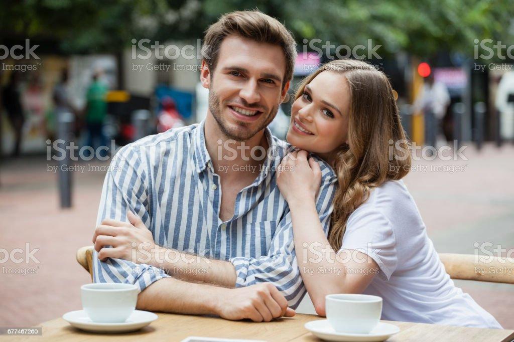 Portrait of happy couple sitting at sidewalk cafe stock photo