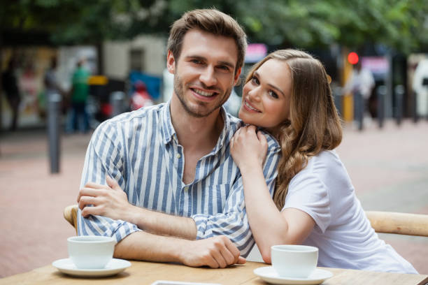 Portrait of happy couple sitting at sidewalk cafe Portrait of happy couple sitting at sidewalk cafe in city age contrast stock pictures, royalty-free photos & images