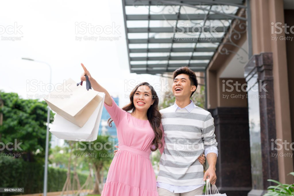 Portrait of happy couple with shopping bags after shopping in city smiling and huging. stock photo