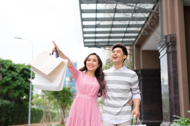 Portrait of happy couple with shopping bags after shopping in city smiling and huging. Portrait of happy couple with shopping bags after shopping in city smiling and huging. shopping couple asian stock pictures, royalty-free photos & images