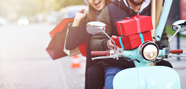 istock Portrait of happy couple with shopping bags on scooter after shopping in city 1055612712