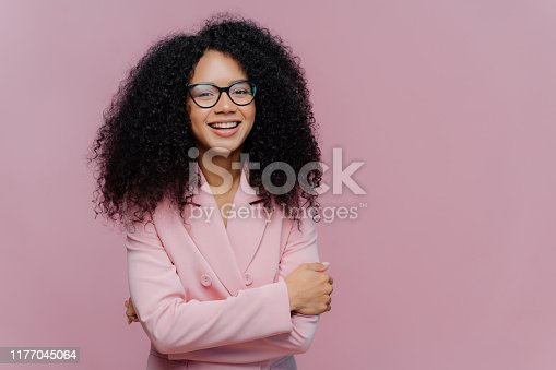 Portrait of happy curly haired businesswoman wears formal jacket, laughs positively, enjoys successful business meeting, has optical glasses, isolated over purple background blank space for your promo