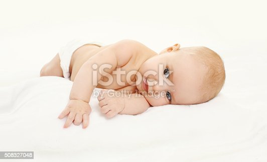 1084486306 istock photo Portrait of happy cute baby playing lying on side 508327048