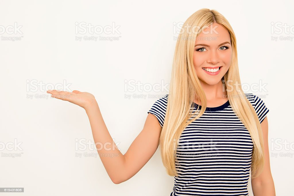 Portrait of happy cute young woman showing product stock photo