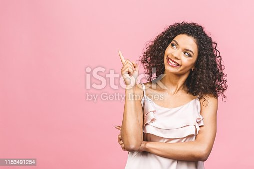 Portrait of happy dark skinned mixed race female model indicates with fore finger at blank copy space, shows place for your advertisement or promotional text. Lovely African American girl.