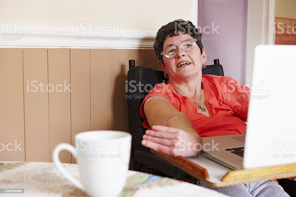 portrait of happy disabled woman working on laptop stock photo