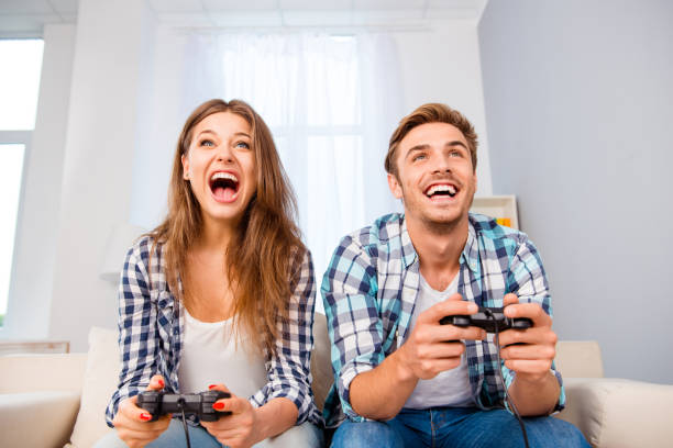 portrait of happy excited family playing video games - gamer paar stock-fotos und bilder