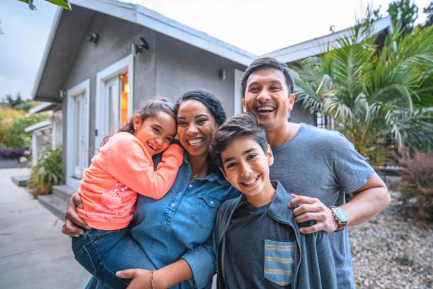 porträt glücklicher familie gegen haus - eigenheim stock-fotos und bilder