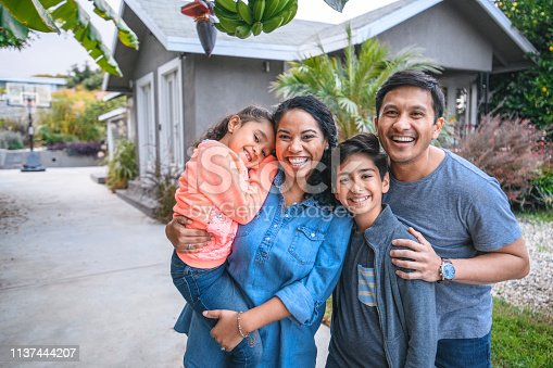 Portrait of happy family against house. Multi-ethnic parents and children are smiling on driveway. They are having fun together during weekend.