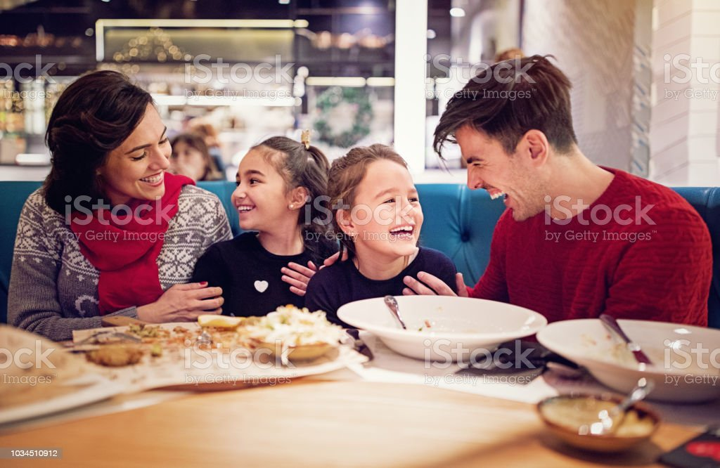 Portrait of happy family eating in the restaurant at Christmas stock photo