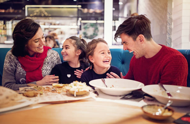 portrait of happy family eating in the restaurant at christmas - being in a relationship with someone is going to require stock photos and pictures