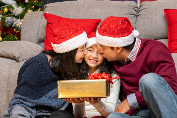 Portrait of happy family, father mother and daughter, celebrate Christmas in living room, holiday season Portrait of happy family, father mother and daughter, celebrate Christmas in living room, holiday season little girl kissing dad on cheek stock pictures, royalty-free photos & images