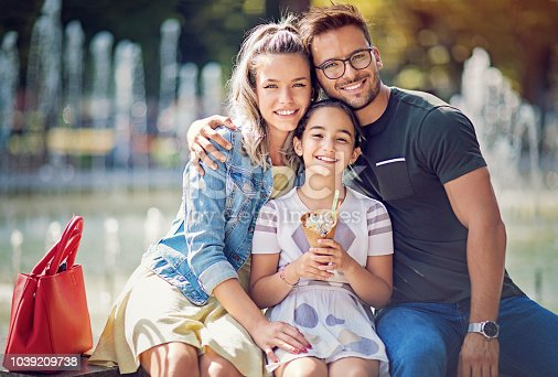 Portrait of happy family hugging and eating ice cream together