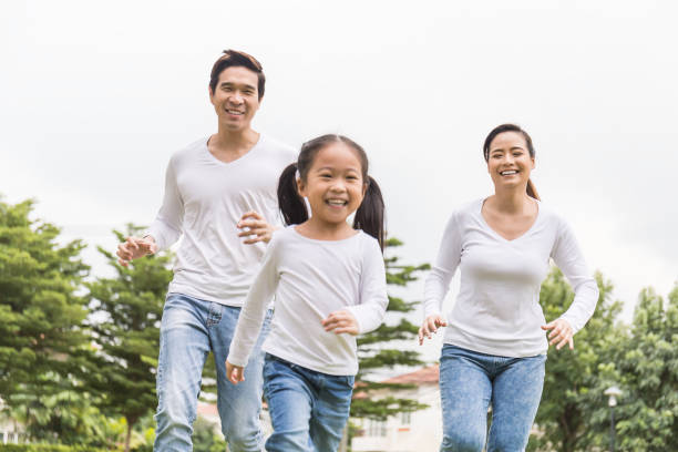 Portrait of happy family mother father daughter exercise running in the park spring summer time.  Health care together love lifestyle concept Portrait of happy family mother father daughter exercise running in the park spring summer time. Asian parent man woman and little girl smile playing in the park. Health care together love lifestyle concept korean ethnicity stock pictures, royalty-free photos & images