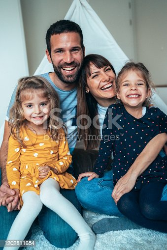 Portrait of family - mother, father and little girls twins smiling and looking at camera sitting at home in front of tent like roof