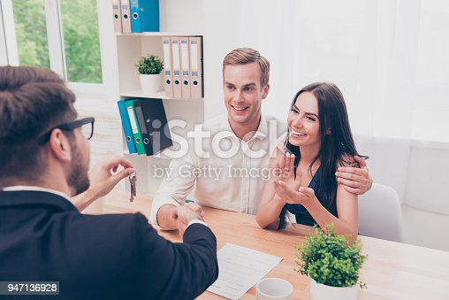 963814372istockphoto Portrait of happy family reach agreement with real estate agent 947136928