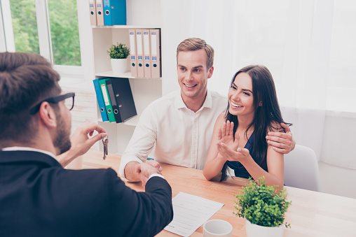 938640610 istock photo Portrait of happy family reach agreement with real estate agent 947136928