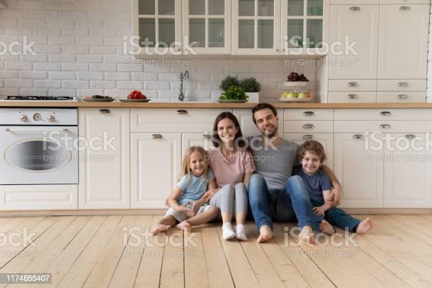 Portrait of happy family sitting on floor at kitchen picture id1174655407?b=1&k=6&m=1174655407&s=612x612&h=fewttxrr4j8xv2hvjq 4gocvizgrumm4brhoddh3 yw=