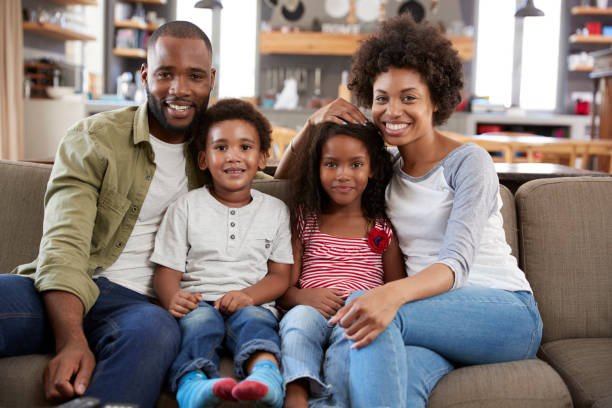 Portrait Of Happy Family Sitting On Sofa In Open Plan Lounge stock photo