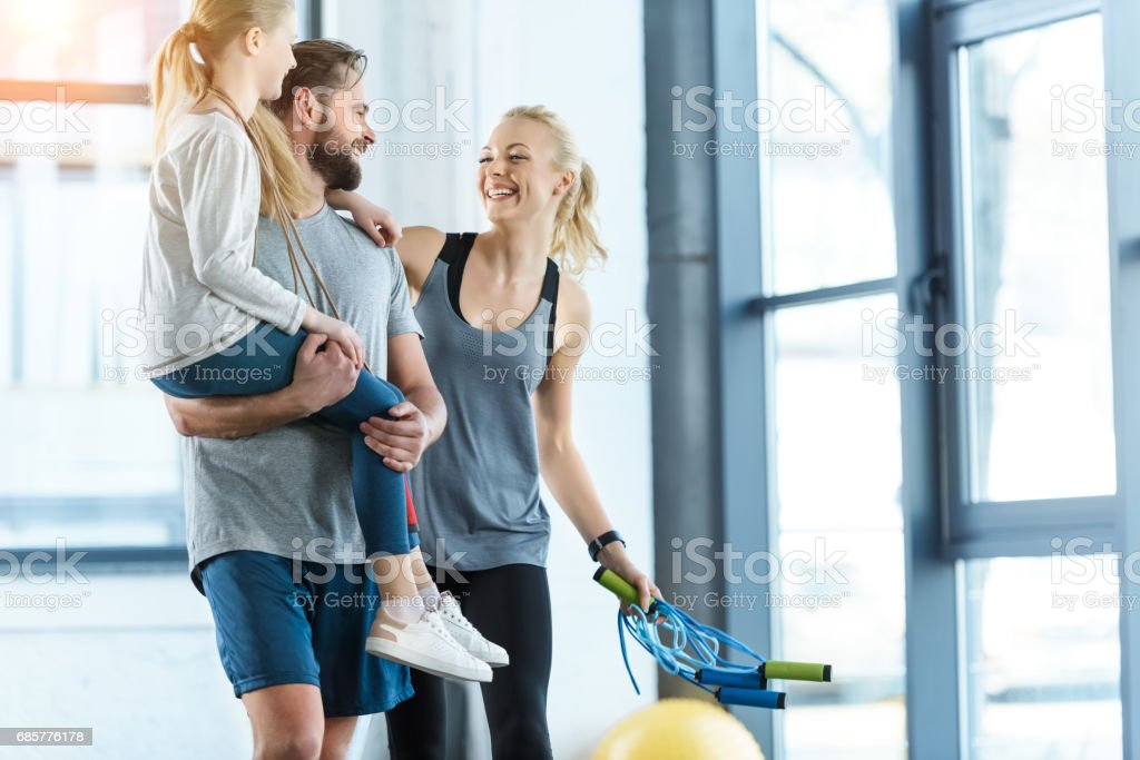 Portrait of happy family standing together at fitness center stock photo