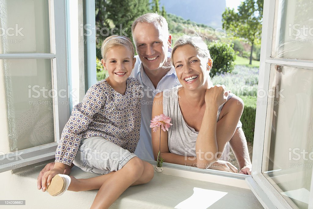 Portrait of happy family with daughter at window royalty-free stock photo