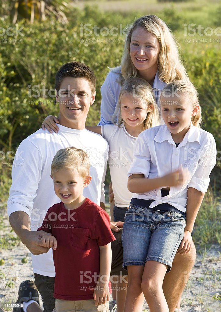 Portrait of happy family with three young blond children outdoor stock photo