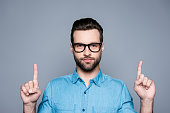 istock Portrait of happy fashionable handsome man in jeans shirt and glasses pointing up with fingers 942806580