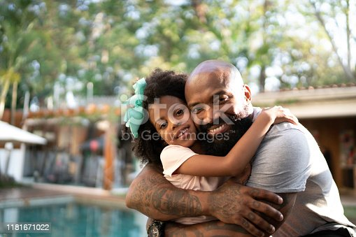 Portrait of happy father hugging his daughter