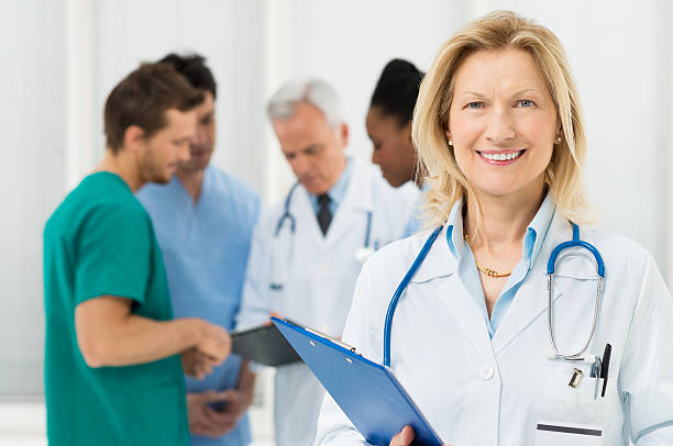 portrait of happy female doctor - female nurse stock photos and pictures