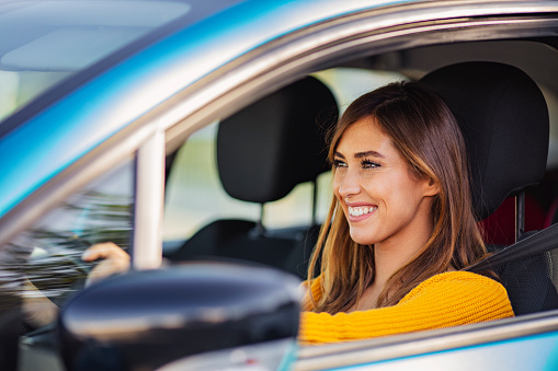 Young woman sitting in a car. Happy woman driving a car and smiling. Portrait of happy female driver steering car with safety belt. Cute young lady happy driving car.