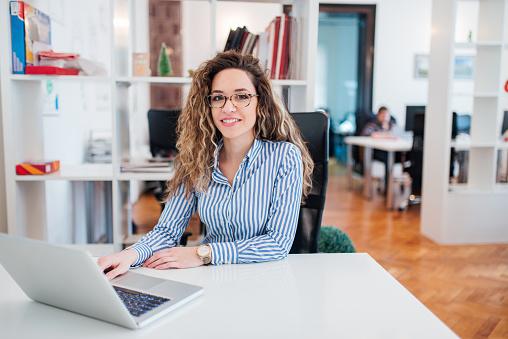 istock Portrait of happy female office worker. 1127110392