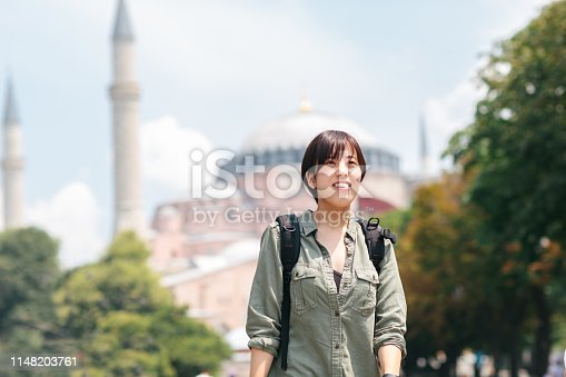 A portrait of a happy female solo traveler while exploring her travel destination.