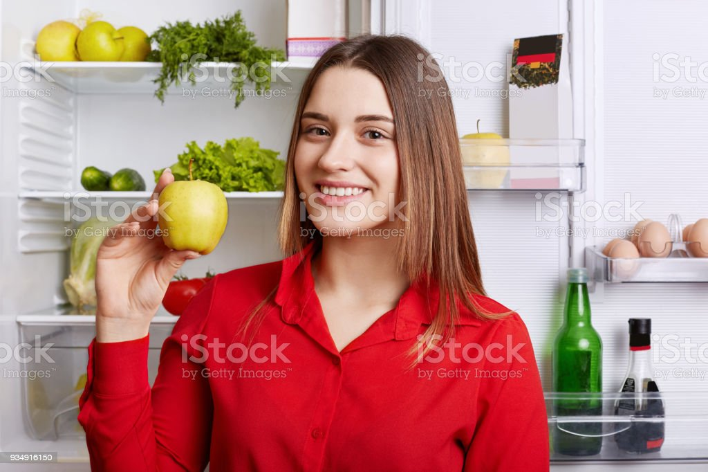Portrait of happy female vegeterian holds fresh apple, stands near fridge with happy expression, keeps to diet, has fridge full of vegetables and fruit. Smiliing woman satisfied with her nutrition stock photo