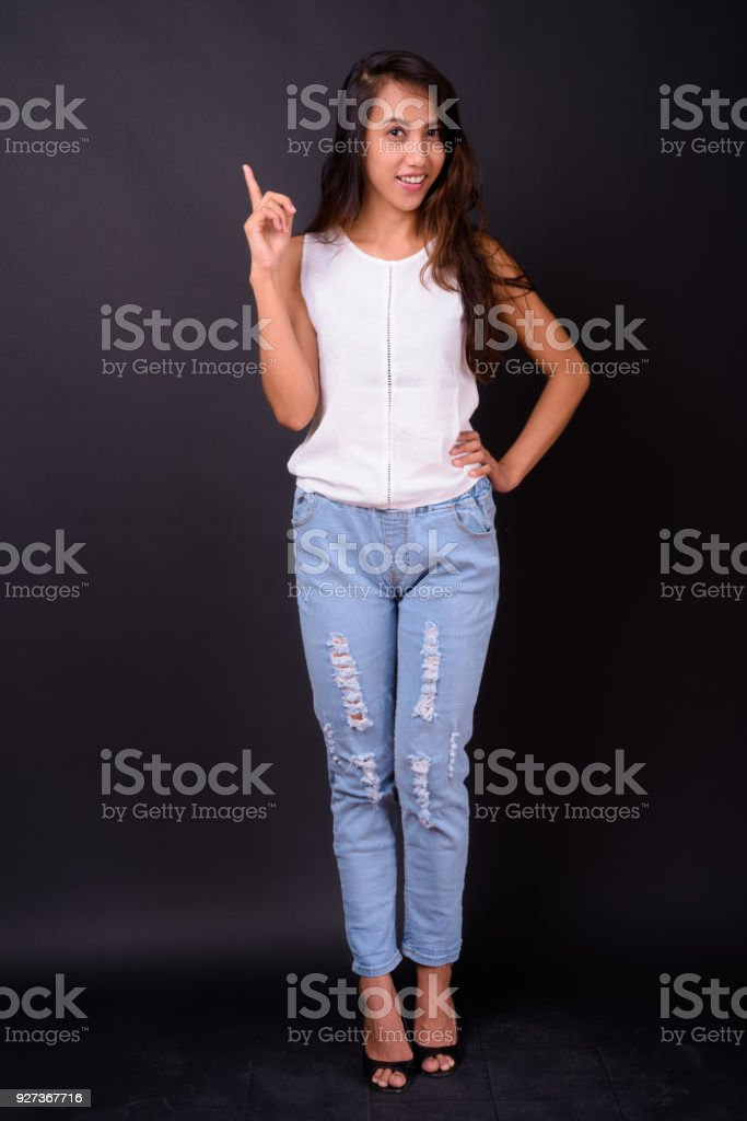Portrait Of Happy Filipino Woman Smiling Against Black Background - Royalty-free 25-29 Years Stock Photo